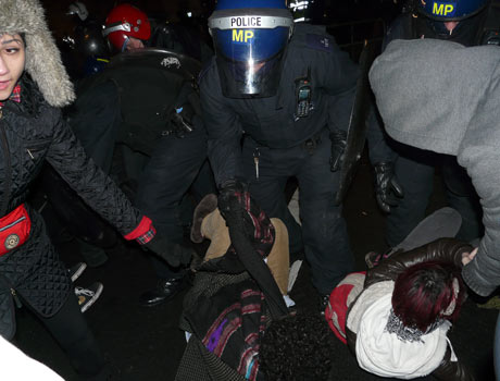 Police lifting a protester by their scarf on 9 December 2010.