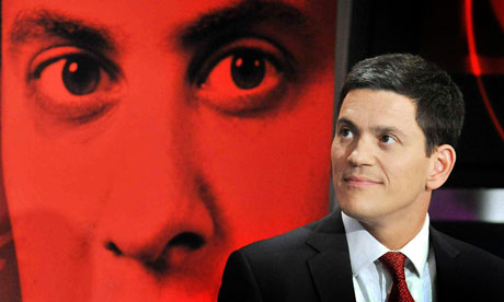 David Miliband in front of a photo of his brother Ed Miliband in September 2010.