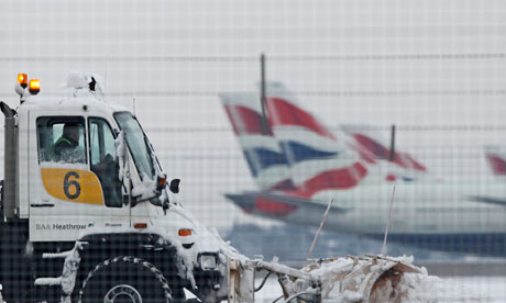 A snow plough is driven by a worker at Heathrow Airport in west London