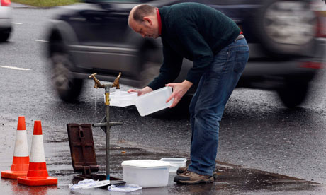 A man fills plastic containers with water from a standpipe in Belfast