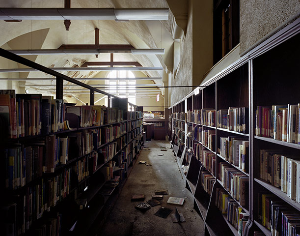A photo of a library in disrepair.  Books line shelves or are on the ground, light filters through a dirty window and the paint is peeling from the ceiling