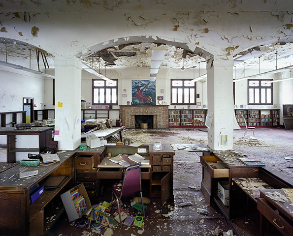 A ransacked desk is in the foreground, with draws pulled open and a box of what appears to be brightly coloured Children's Books spilled onto the floor.  The pain in the wide but brightly lit room is peeling and books remain on the shelves on the far walls