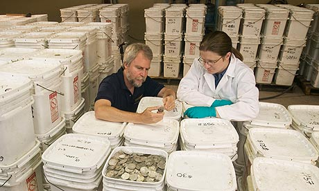 Odyssey staff examine coins recovered from the 'Black Swan' shipwreck