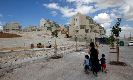 A woman and children walk past apartments under construction in the West Bank Jewish settlement of Maale Adumim
