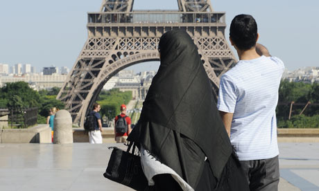 A woman wearing a niqab walks near the Eiffel Tower in Paris.