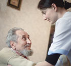 Social care worker helping elderly man