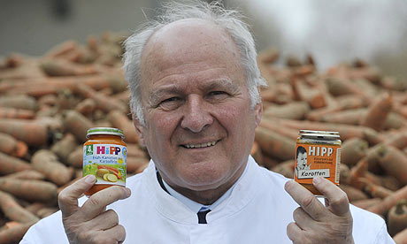 Claus Hipp with two jars of Hipp baby food at the company's German  HQ