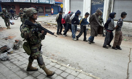 Chilean soldiers detain a group of looters in Talcahuano, Chile, after the earthquake.