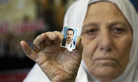 The mother of Hamas militant Mahmoud al-Mabhouh holds a photo of him