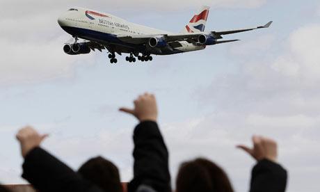 Picketing British Airways workers gesture towards a landing plane at Heathrow airport