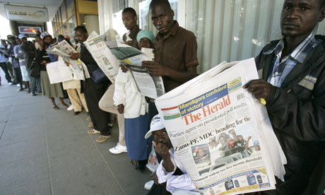 Harare residents read newspaper while they wait in a bank queue