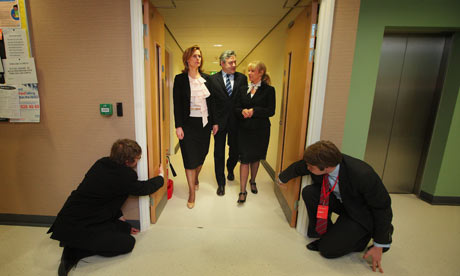 Labour officials hold doors open as Gordon Brown and his wife Sarah walk with Sam Prince (right)