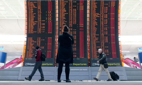 Travellers pass a board showing cancelled flights at the Roissy Charles de Gaulle airport, Paris.