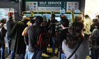 Passengers wait to buy tickets