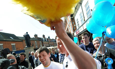 David Cameron holds up the mask of a Daily Mirror man dressed as a chicken in Tamworth