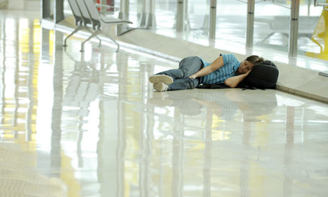 A passenger waits at Madrid Barajas airport after some planes remained grounded.