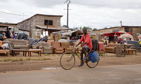A man cycles past furniture for sale at the roadside in Cameroon.