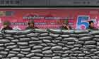 Thai soldiers sits inside their bunker at a bus stop on a business and embassy district