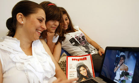 Rana Fakih (L) looks at pictures of her sister, Rima Fakih