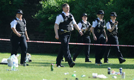 Police officers walk through a cordoned off area of London Fields in Hackney, east London