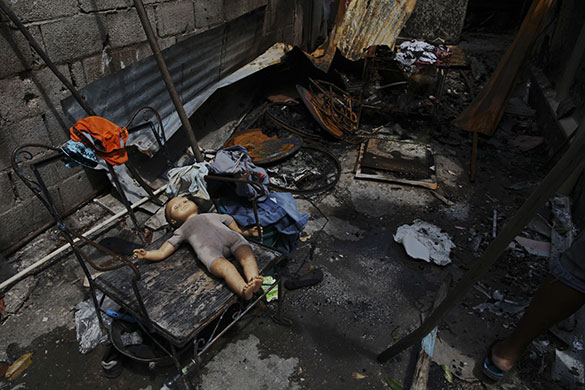 24 hours in pictures: Kingston, Jamaica: A doll on the floor of a house that was burnt