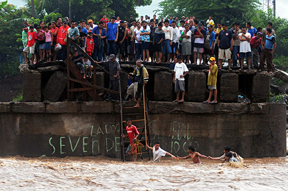 24 hours in pictures: La Libertad, El Salvador: People try to cross the overflowed Huiza river