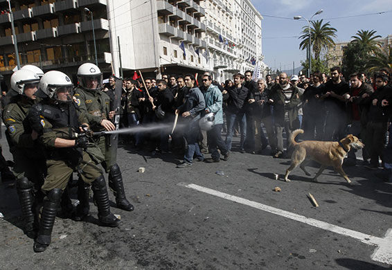 Greek riots dog: 24 February: Police officers spray teargas against protesters in Athens