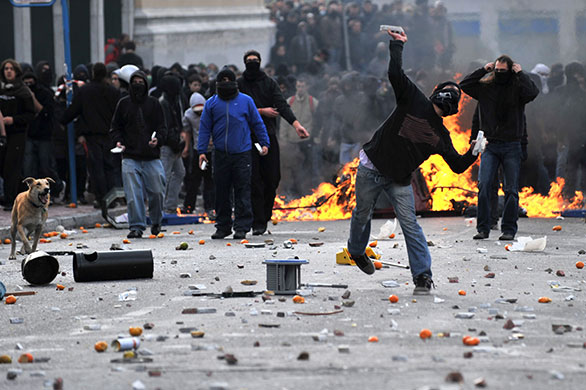 Greek riots dog: 6 December 2009: A demonstrator throws a stone at riot police