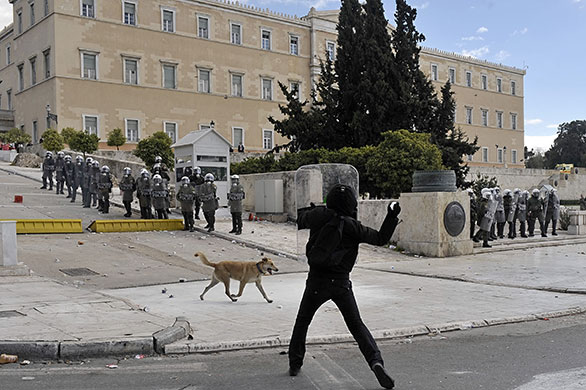 Greek riots dog: 5 March 2010: A protester uses a police shield while thowing stones