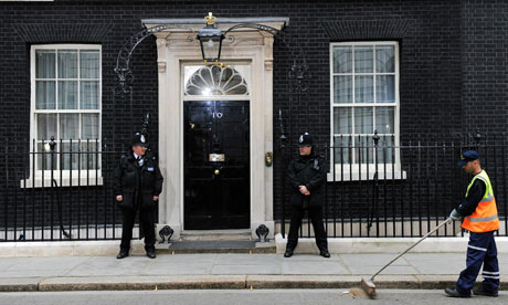 A council worker sweeps Downing Street