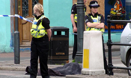 Police stand next to a body following a shooting on  Duke Street, Whitehaven, Cumbria.