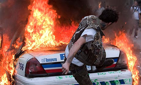 A protester kicks a burning police car in Toronto