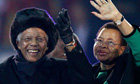 Nelson Mandela and his wife Graca Machel wave to fans at Soccer City stadium