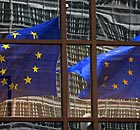 EU flags reflecting off the EU headquarters in Brussels