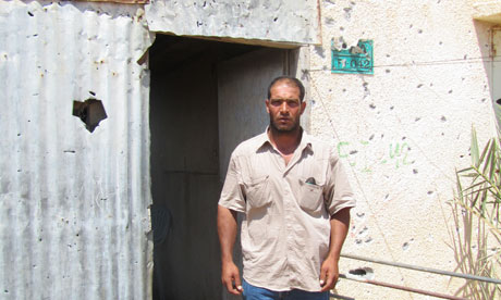 Nasser Abu Said outside the shrapnel-riddled home where wife  Ne'ema was killed by Israeli artillery