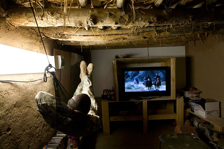 24 hours in pictures: A US soldier watches an Afghan film on TV at Combat Outpost Nolen, Afghanistan