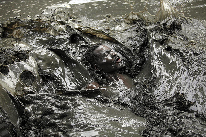 24 hours in pictures: Haiti: A voodoo believer swims in a mud pool
