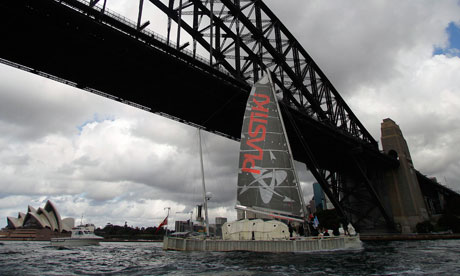 The Plastiki catamaran is towed under the Sydney Harbour Bridge
