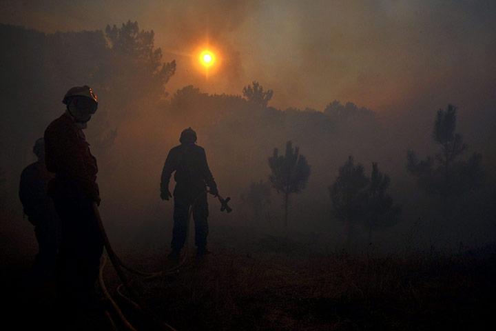 24 hours: Fragosela Viseu, Portugal:  A fireman tries to extinguish a forest fire