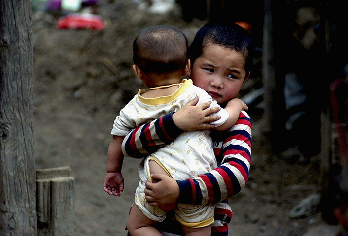 24 hours pictures: A boy holds his brother and walks through the scene of a mudslide, China