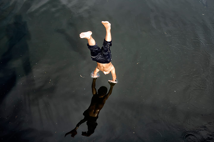 24 hours pictures: A boy dives into the Dambovita river to cool off in Bucharest