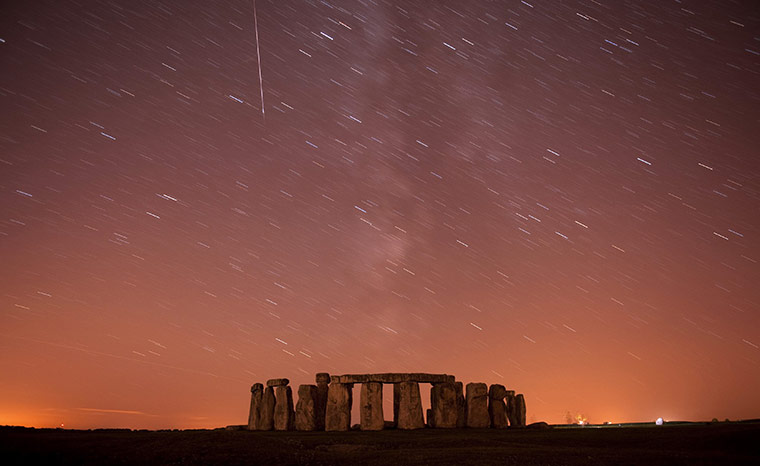 Perseid meteors: A meteor streaks past stars in the night sky over Stonehenge
