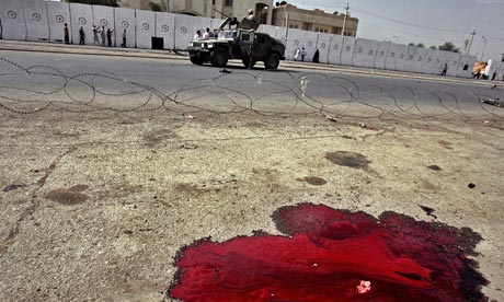 US soldiers drive past a pool of blood from a car bomb in Baghdad during October 2006