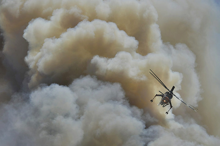 A firefighting helicopter flies through smoke from a wildfire in Vari,Greece
