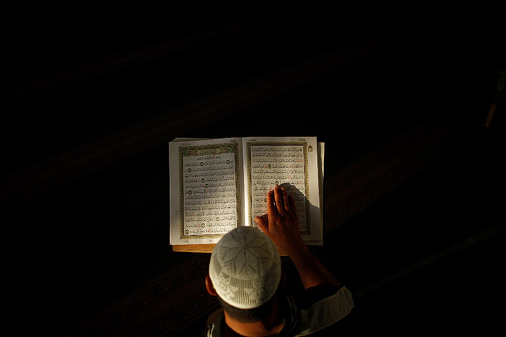 Ramadan: A Palestinian Muslim man reads from the Qur'an in Ramallah