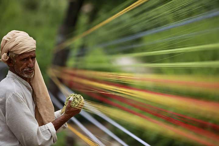 24 hours in pictures: Jammu, India: A  thread maker prepares coloured thread for flying kites