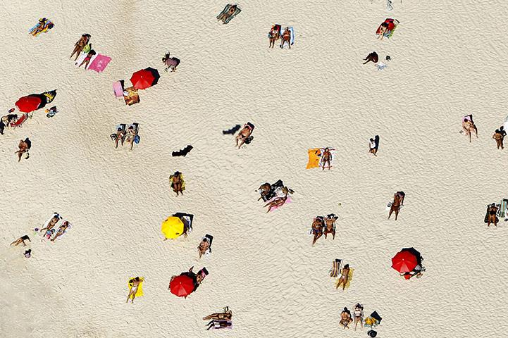 24 hours in pictures: Rio de Janeiro, Brazil: People sunbathe on Flamengo beach