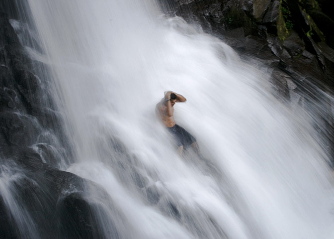 A man sit in the middle of the waterfall before diving in