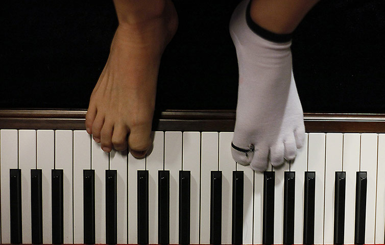 Liu Wei, who lost both his arms in an accident, plays the piano with his toes