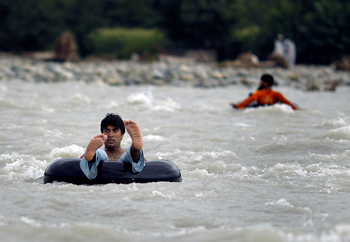 Men use inner tubes from tyres to cross the flooded Swat river